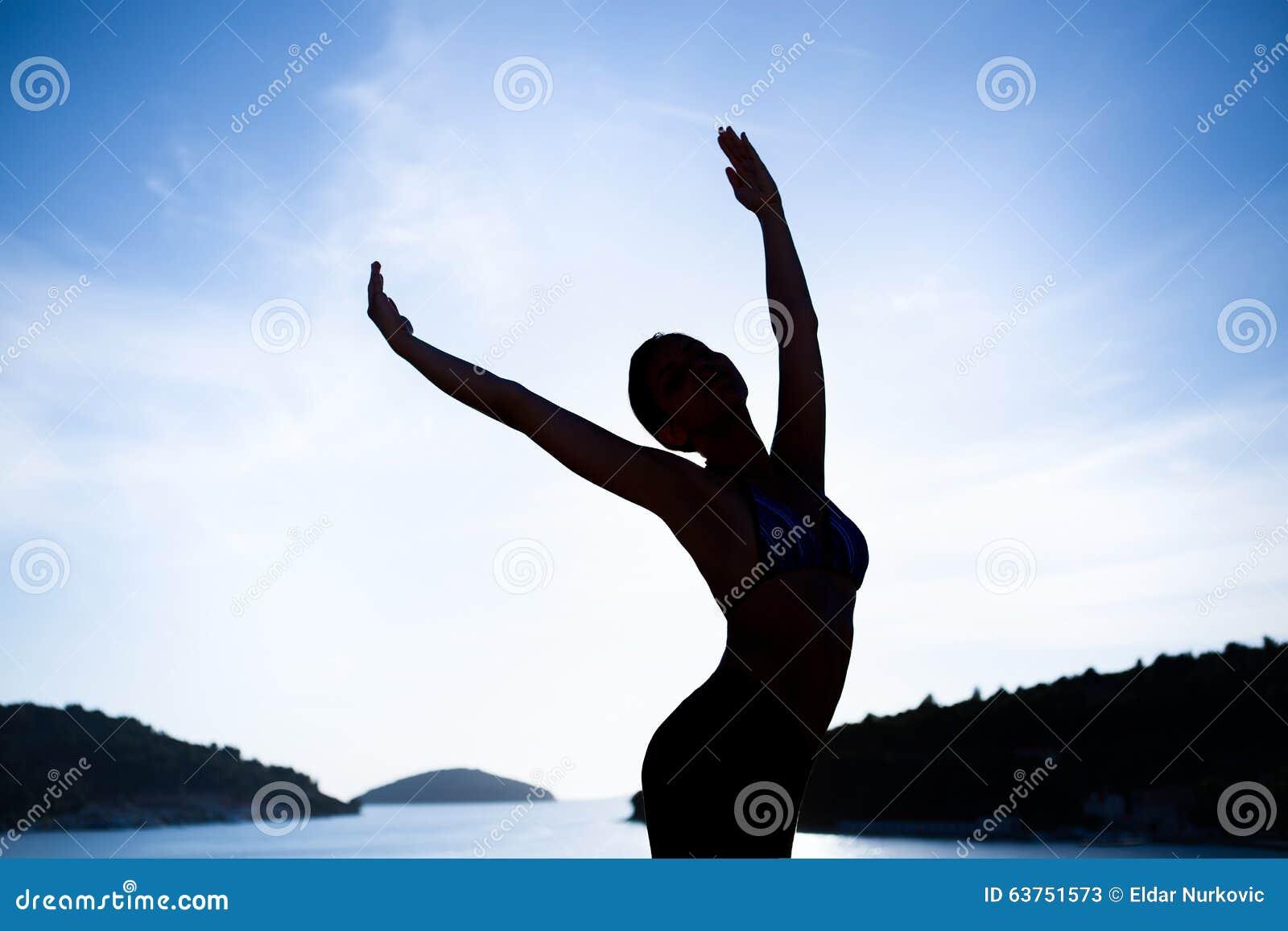 Danse insousiante de femme dans le coucher du soleil sur la plage concept vivant sain de vitalité de vacances