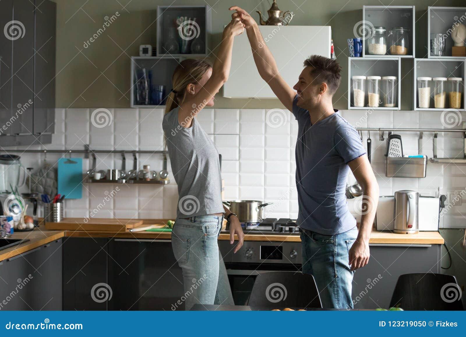 Danse romantique heureuse de couples dans la cuisine tout en faisant cuire le toget
