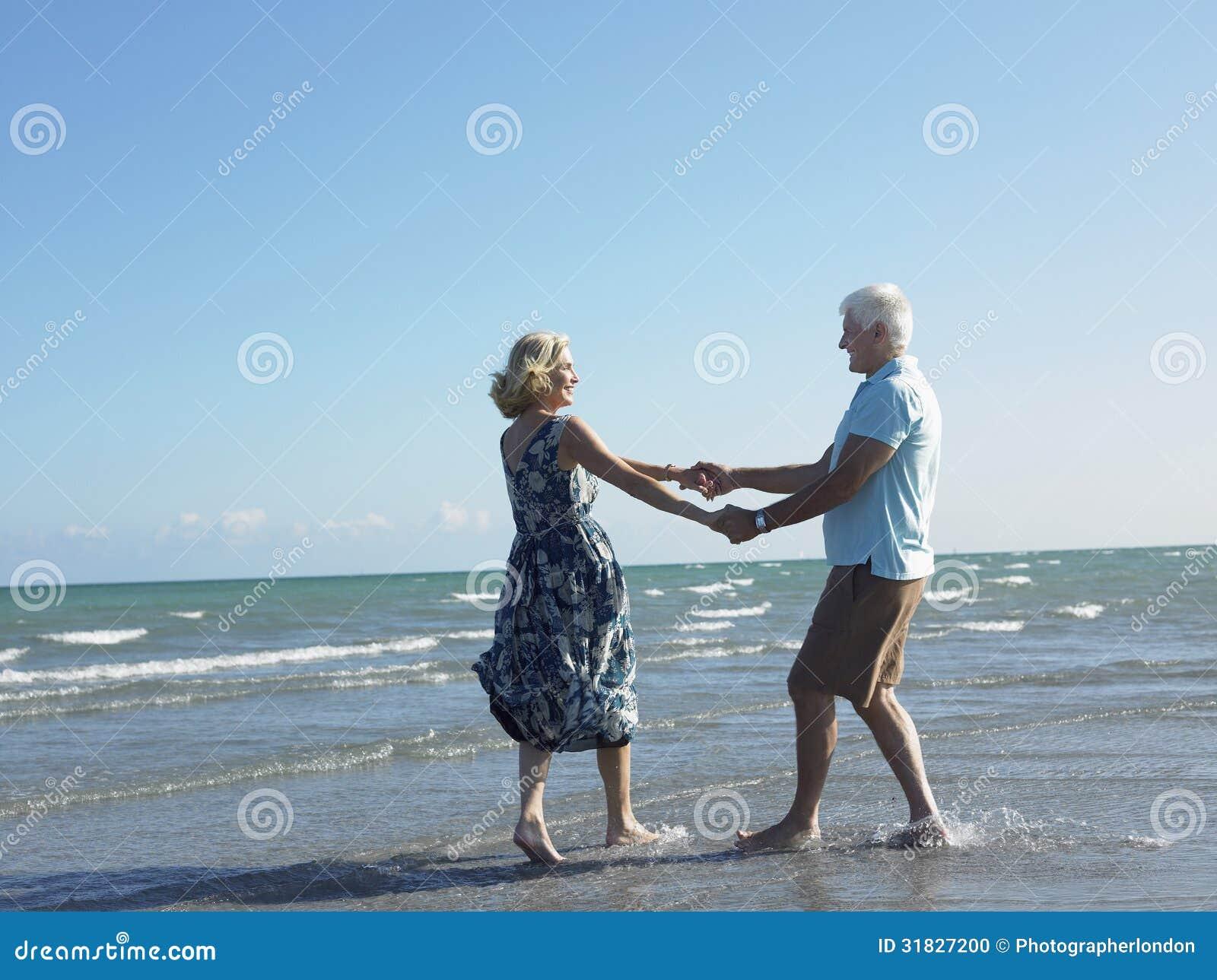 Danse supérieure heureuse de couples sur la plage tropicale