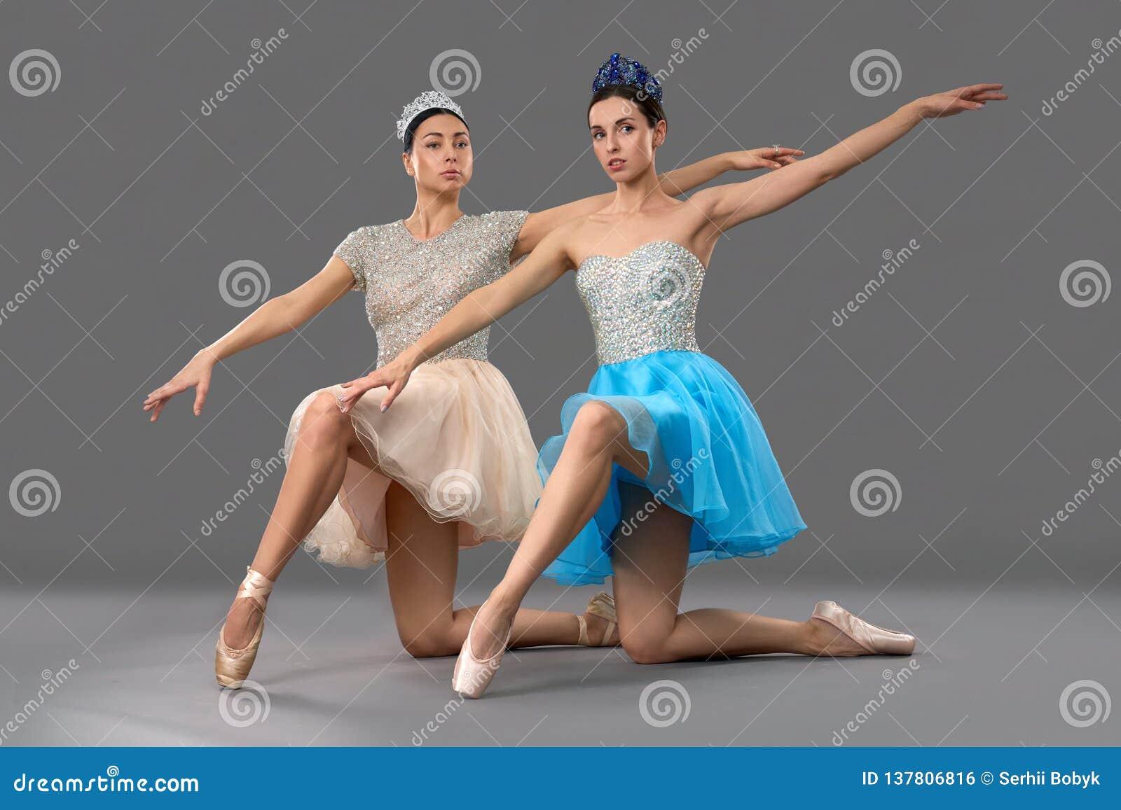 Danseurs classiques adorables s asseyant sur des genoux et soulevant la main
