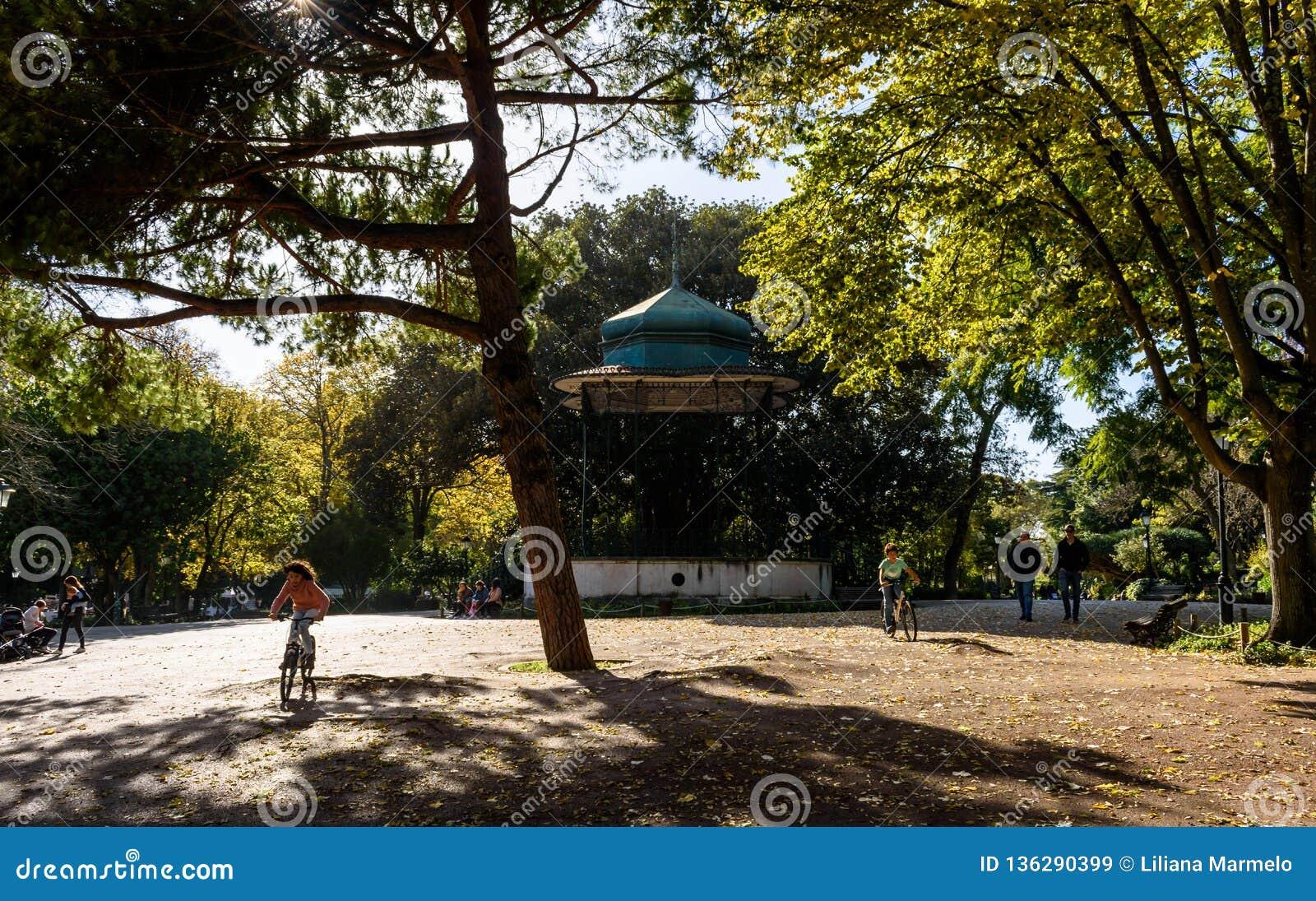 Dar uma volta e crianças dos povos que montam bicicletas em Jardim a Dinamarca Estrela, Lisboa - Portugal