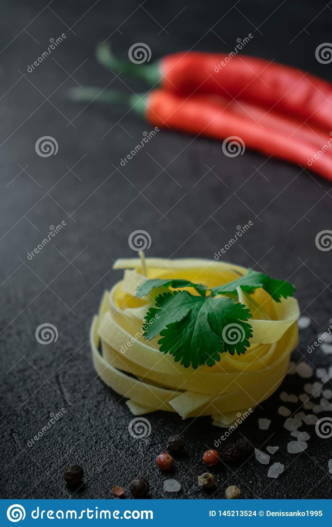 On a dark background raw fettuccine pasta with cilantro leaves, coarse sea salt black and red peppercorns and chili