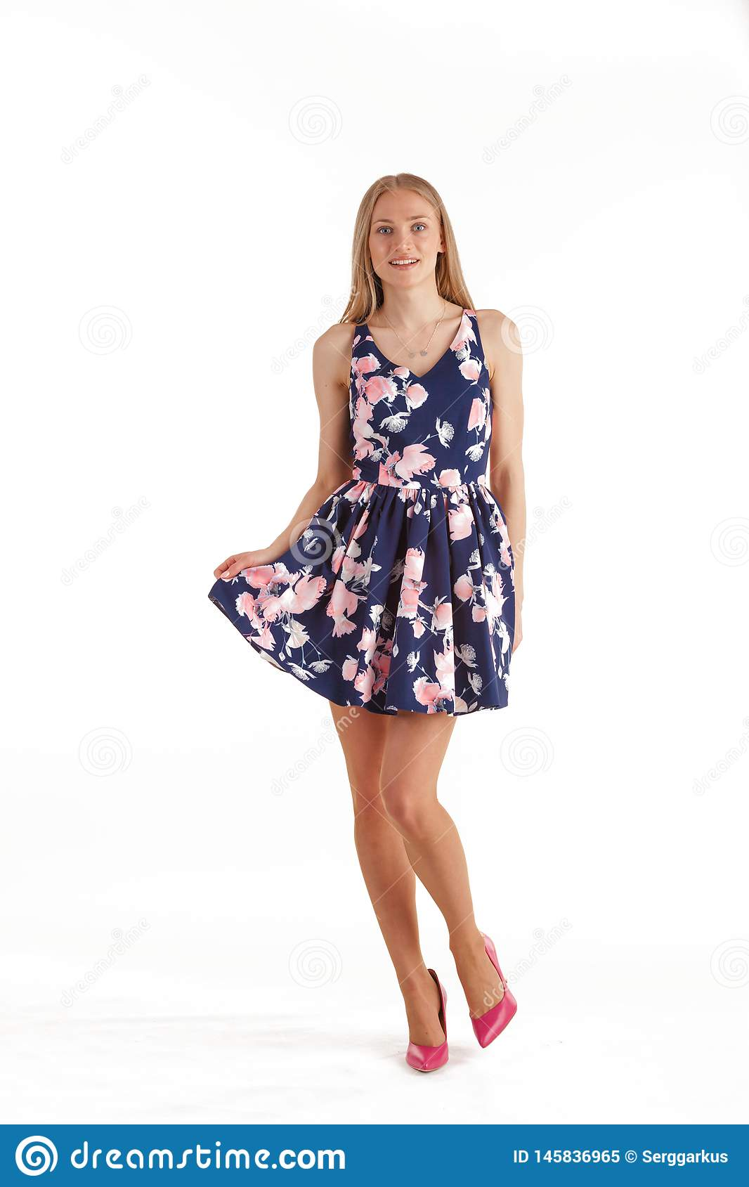 Beautiful young blonde woman in dark blue dress with floral print isolated on white background