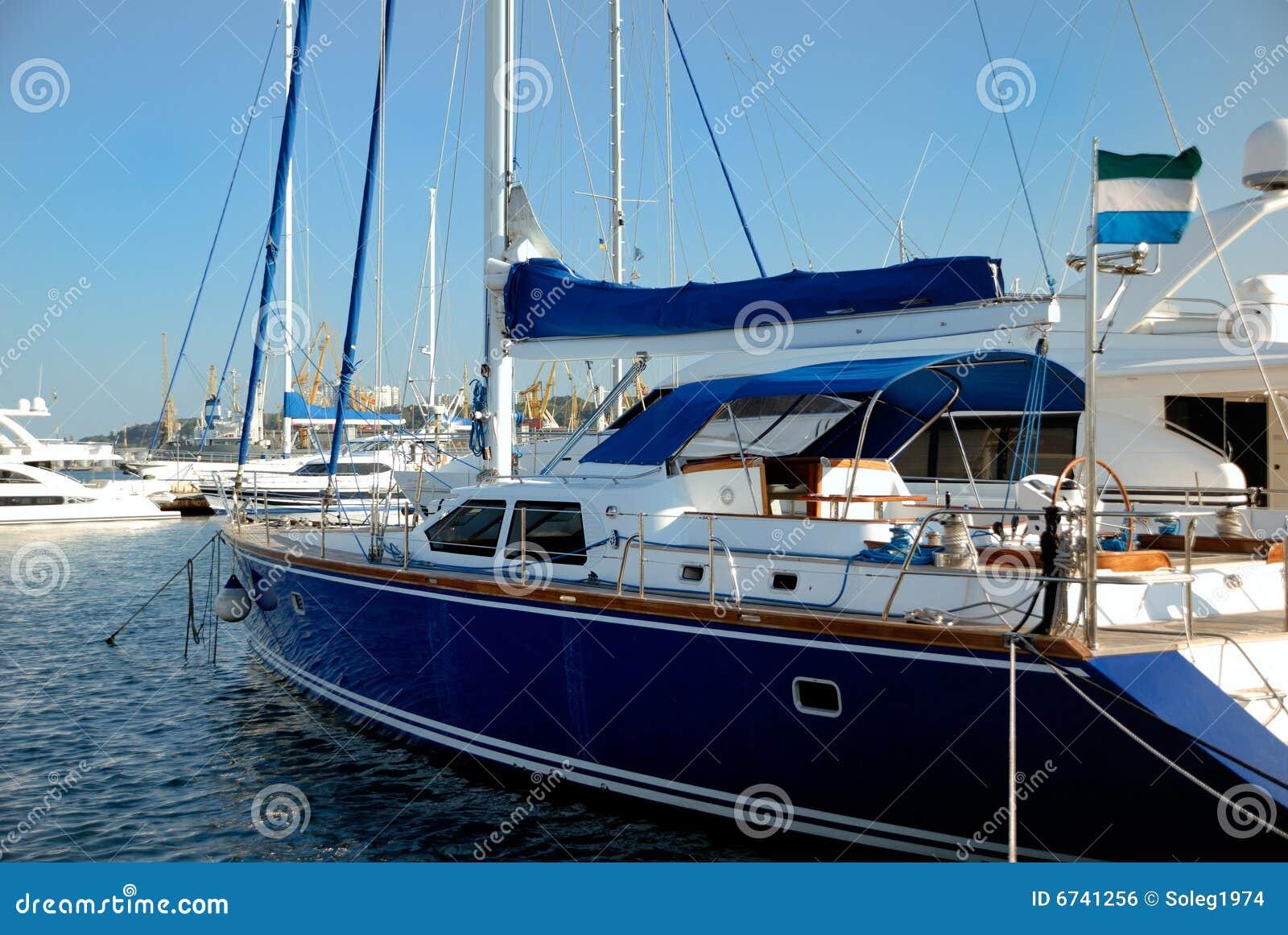 dark blue sailing yacht on an anchor stock photo