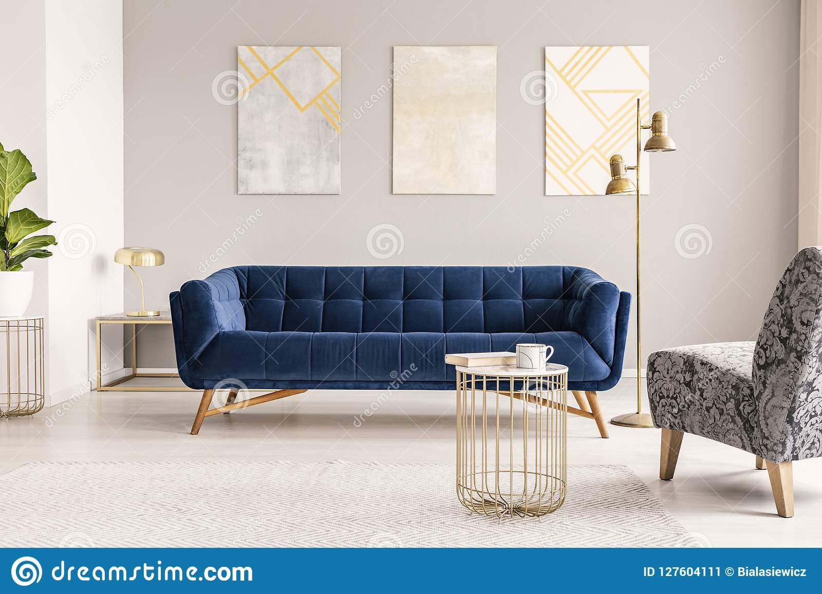 A dark blue velvet settee against a gray wall with modern paintings in an empty living room interior. Real photo.