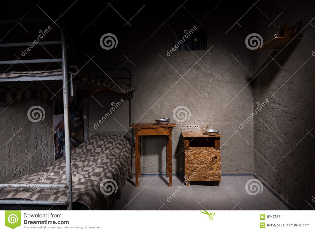 Dark Empty Jail Cell With Iron Bunk Bed And Bedside Table Stock