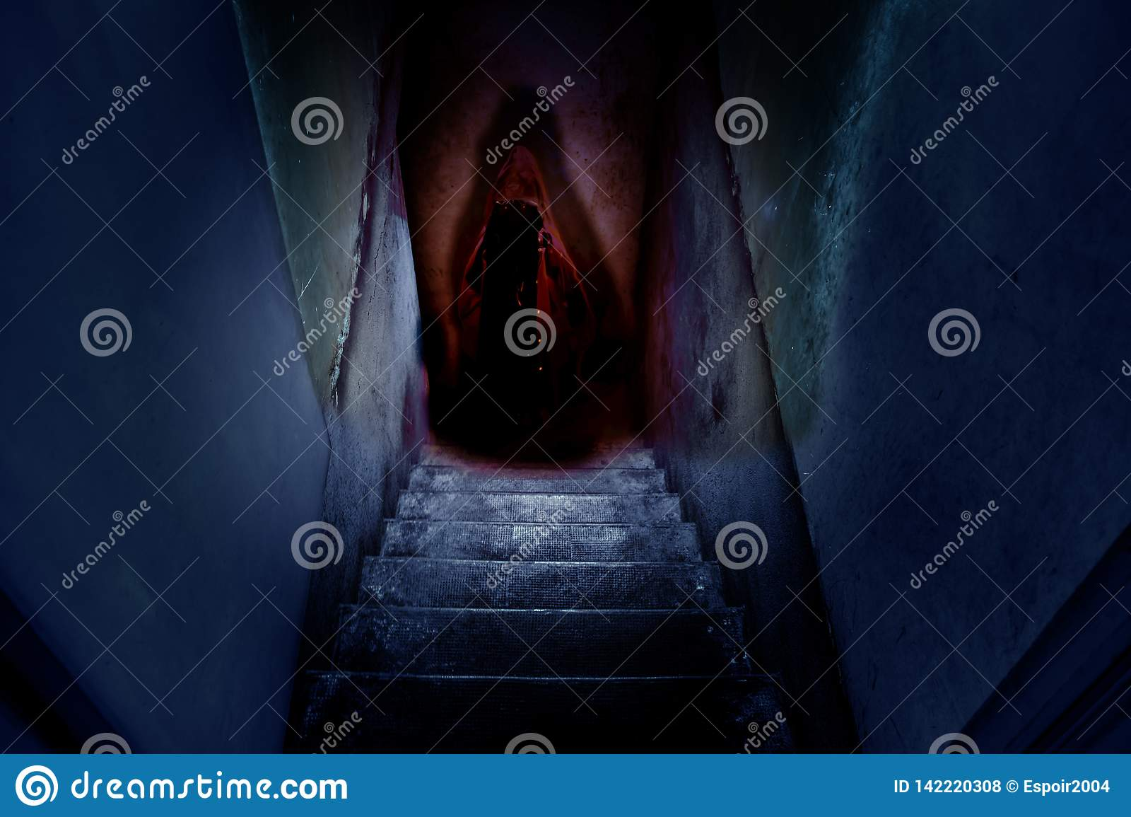 Dark figure in a red cape with a hood on the old concrete stairs in the descent to the basement