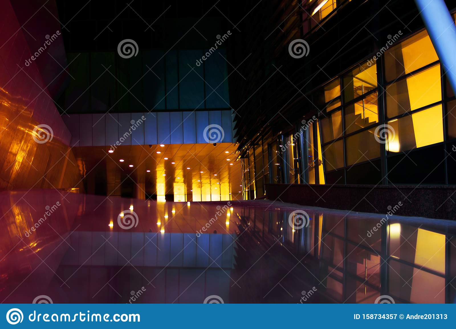 Dark foyer of a modern building illuminated by yellow light