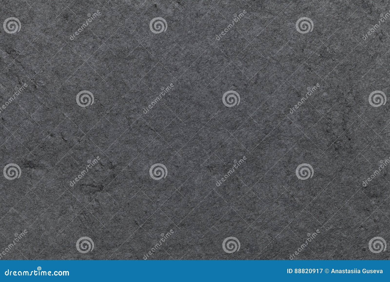 Dark gray background of natural slate. Texture black stone closeup.