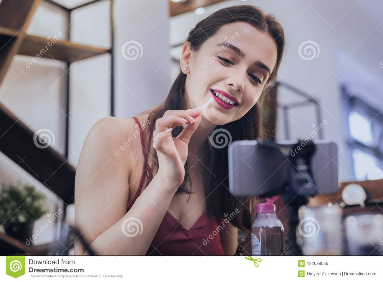 Dark-haired cheerful woman fixing her makeup