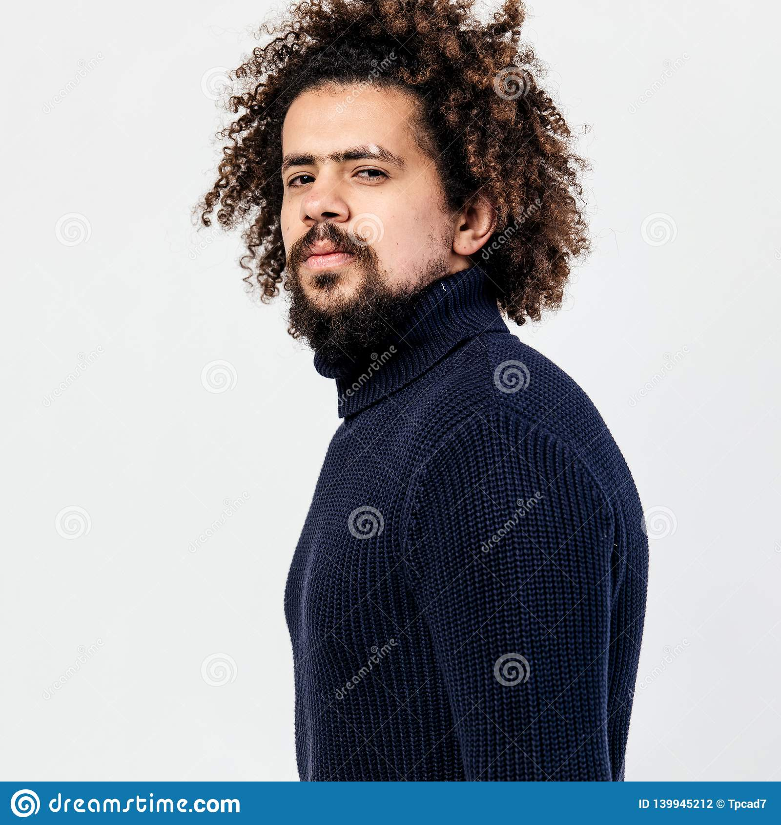 Dark-haired curly guy with a beard dressed in a black knitted turtleneck poses in the studio on the white background.