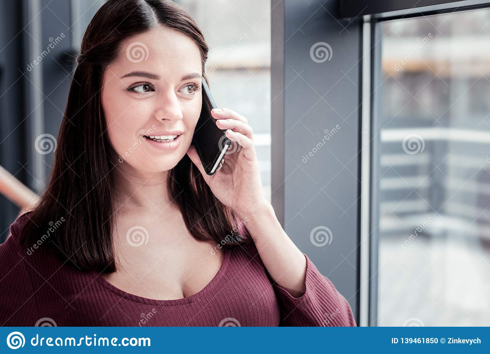 Dark-haired cute woman feeling fascinated while talking by phone
