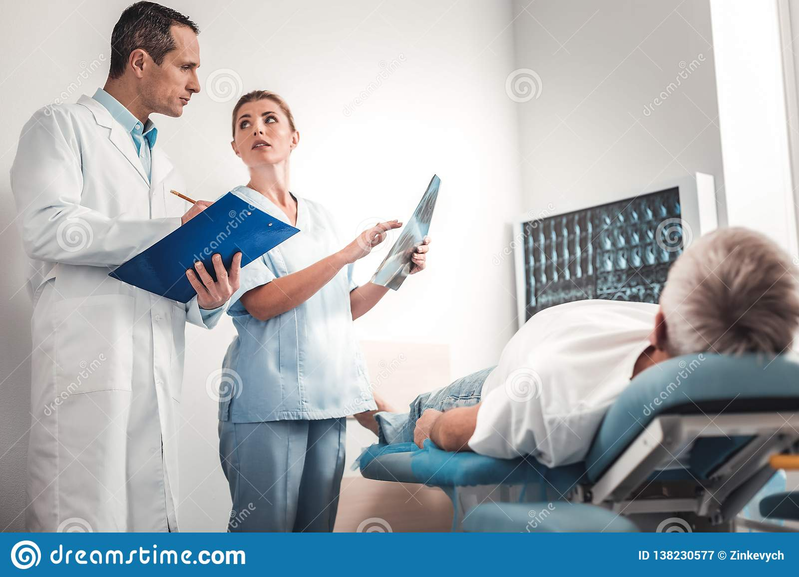 Dark-haired doctor wearing white uniform listening to recommendations