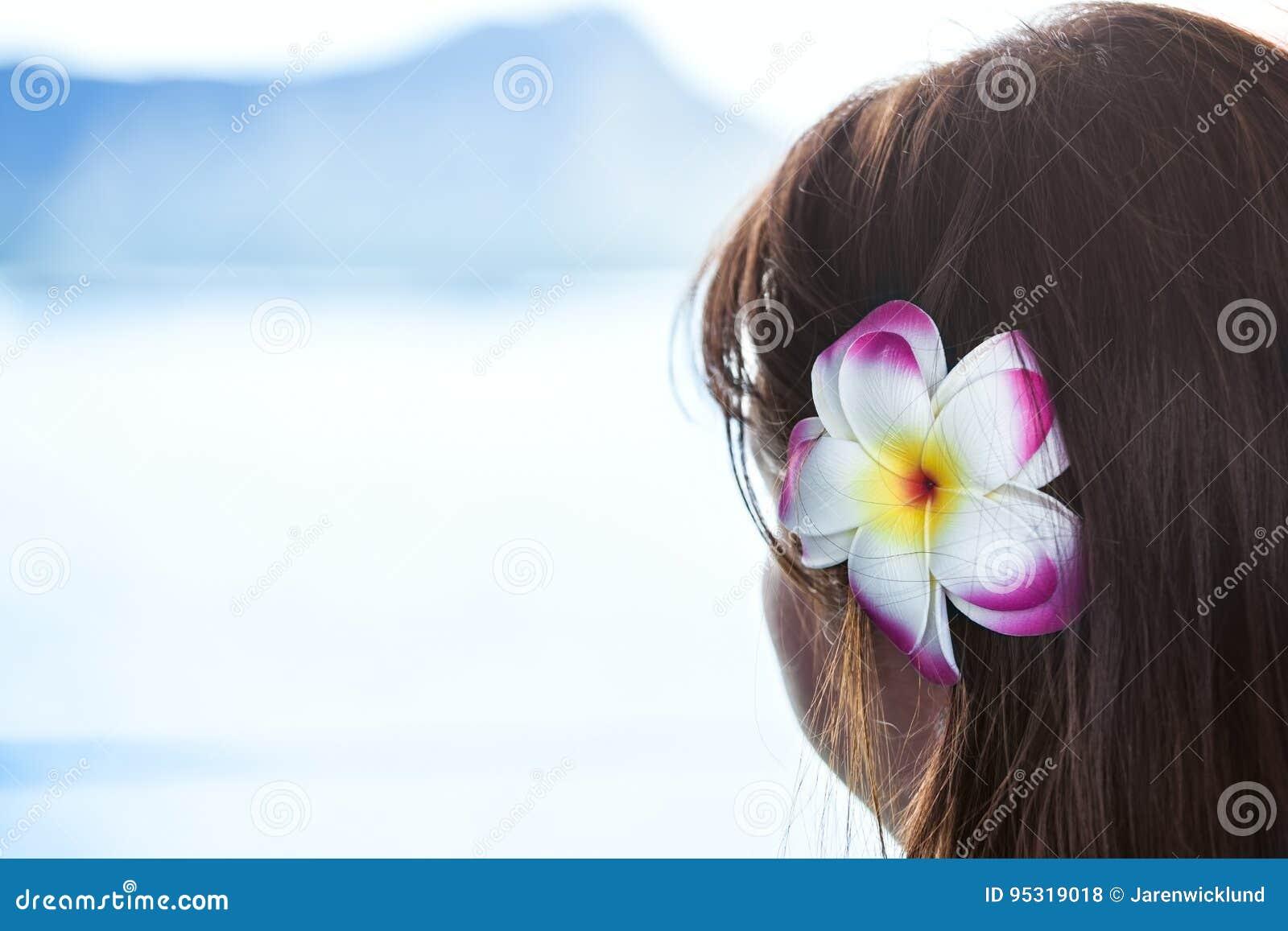 Dark haired girl wearing Hawaiian flower looking at ocean view