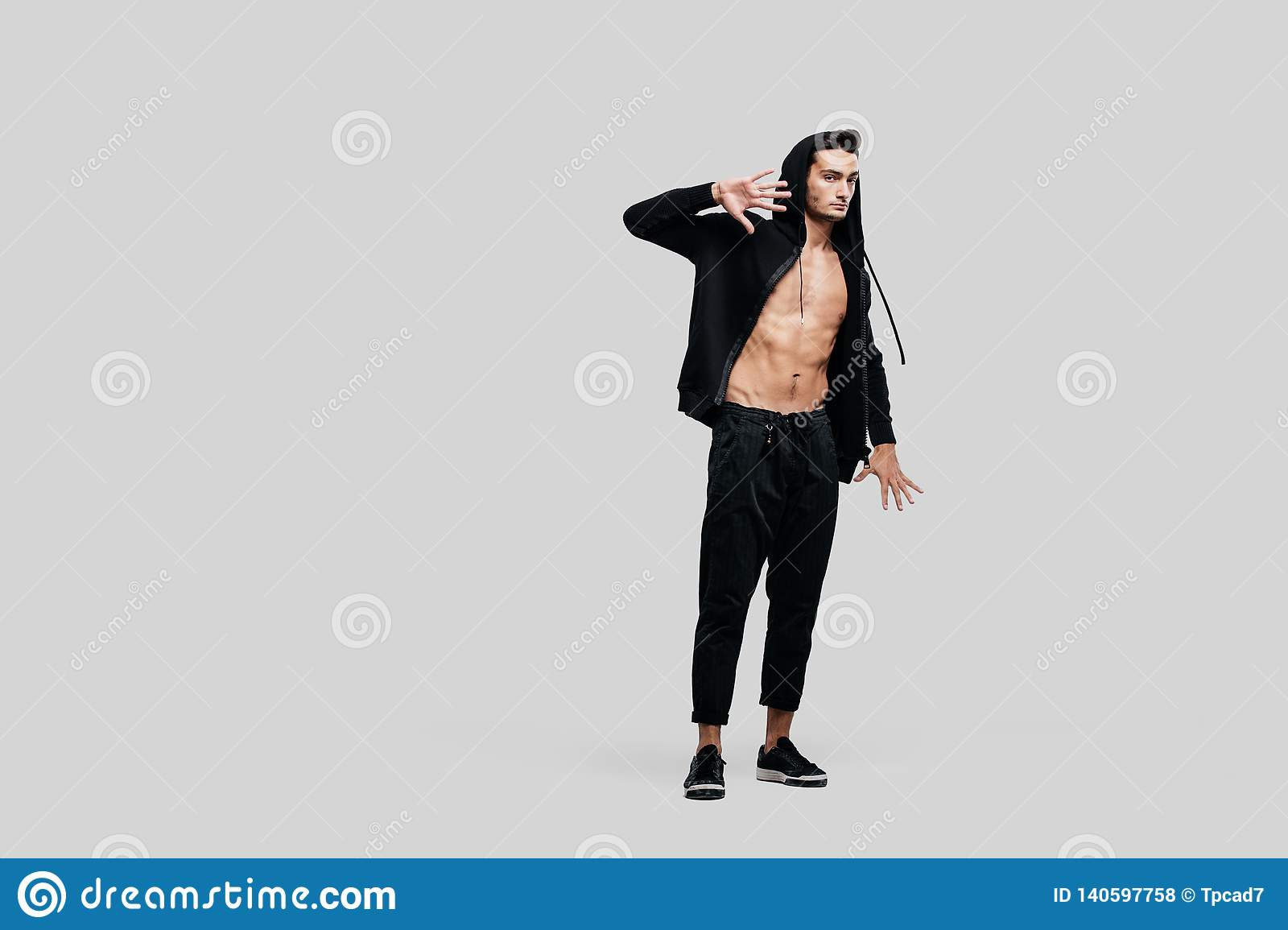 82540ffe Dark-haired handsome dancer wearing sweatshirt on a naked torso and a black  pants stands