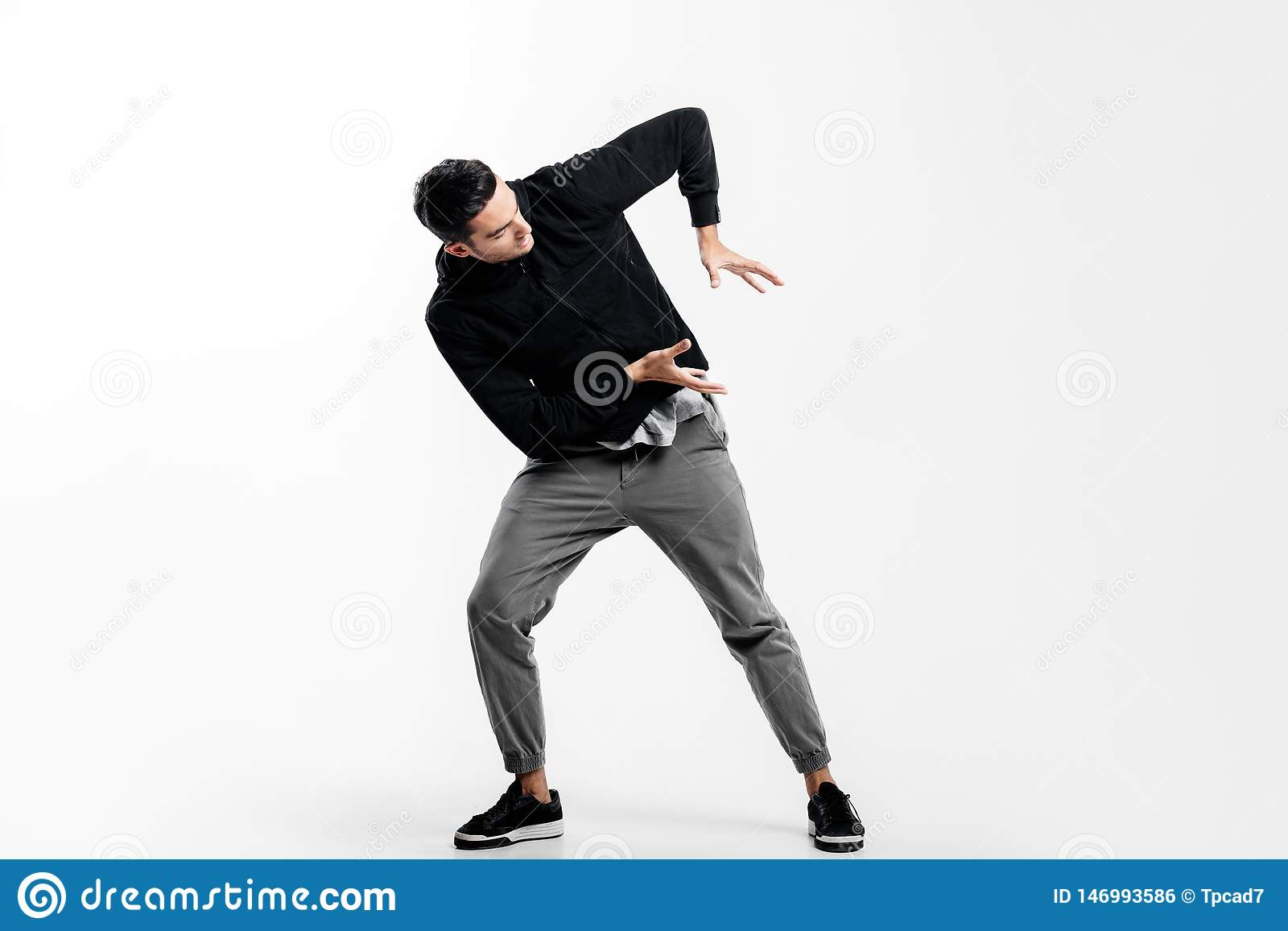 Dark-haired young man wearing a black sweatshirt and gray pants is dancing street dance. He makes stylized movements