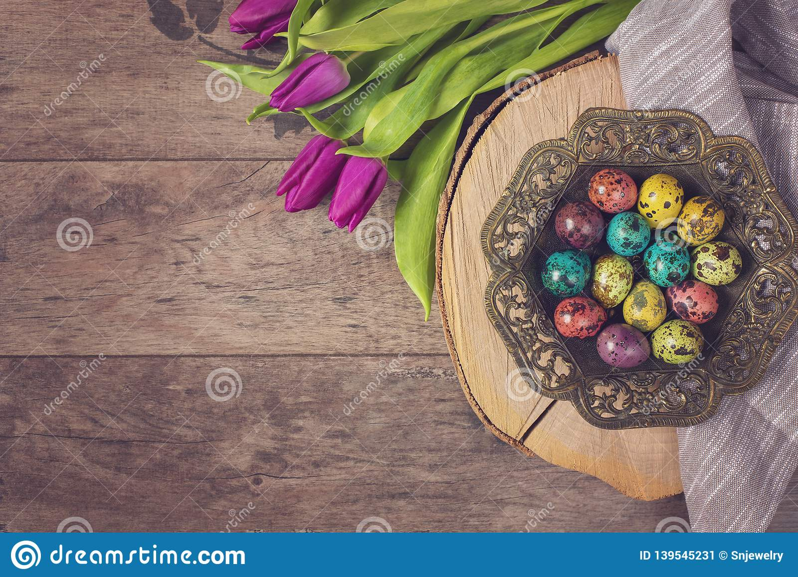 Dark photo of Easter quail eggs in an ancient metal bowl. Beautiful spring flowers - purple tulips on a wooden background. Floral