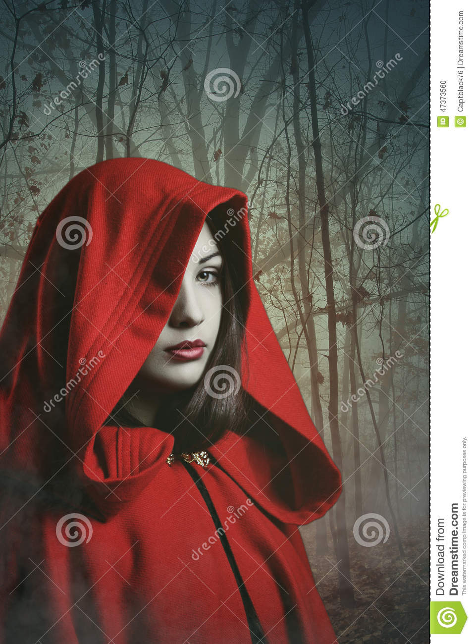dark red hooded woman in a misty forest stock photo