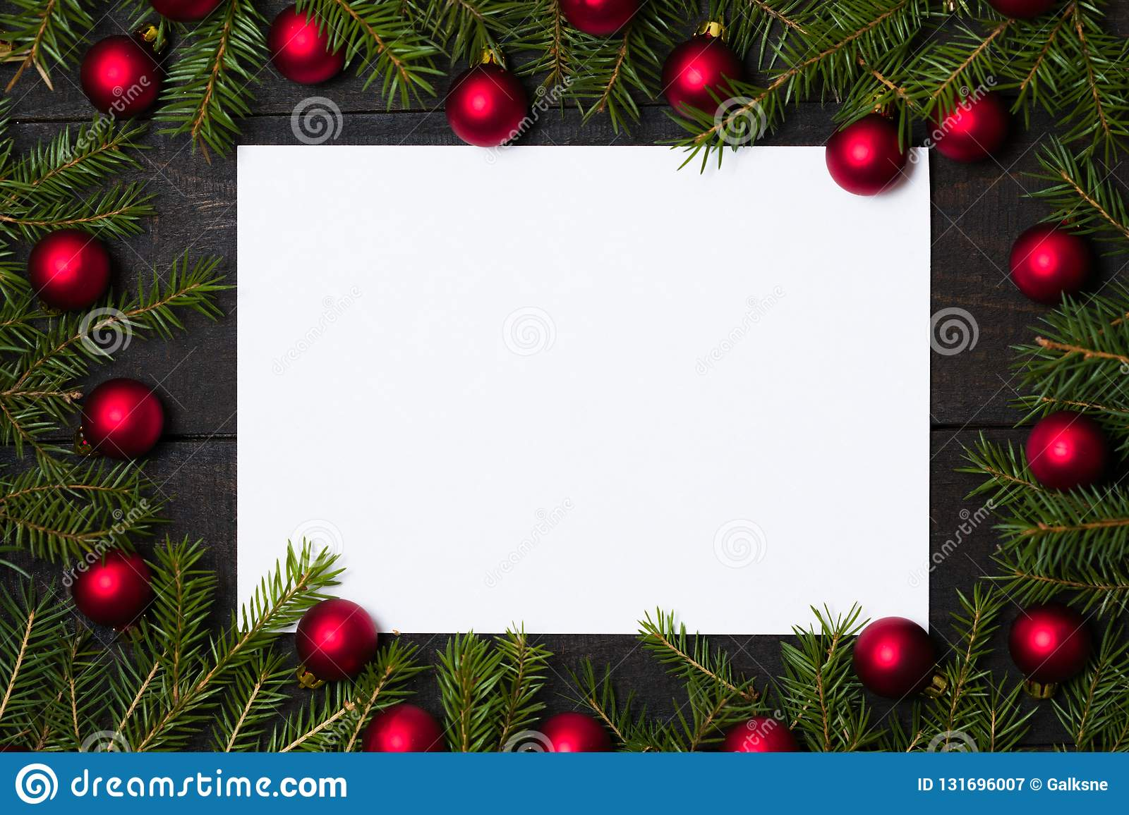 Dark rustic wood table flatlay - empty card on Christmas background with red ball ornament decoration and fir branch frame. Top