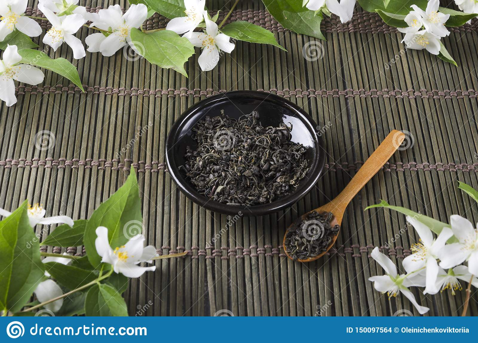 Dark saucer and green tea leaves on it, wooden spoon, fresh jasmine flowers on green serving mat