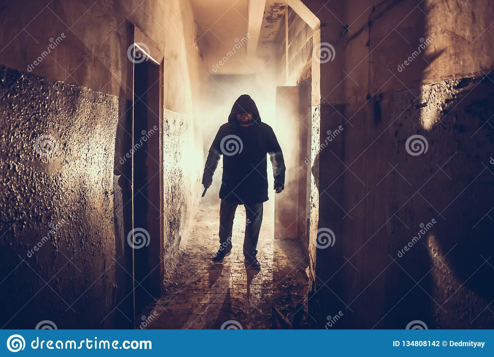 Dark silhouette of strange danger man with knife in hand in scary grunge corridor or tunnel