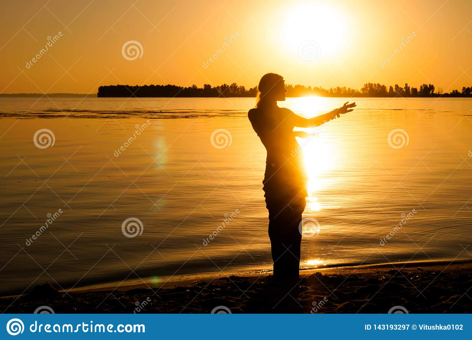 Silhouette of woman dancing tradition trible oriental near big river coast at dawn