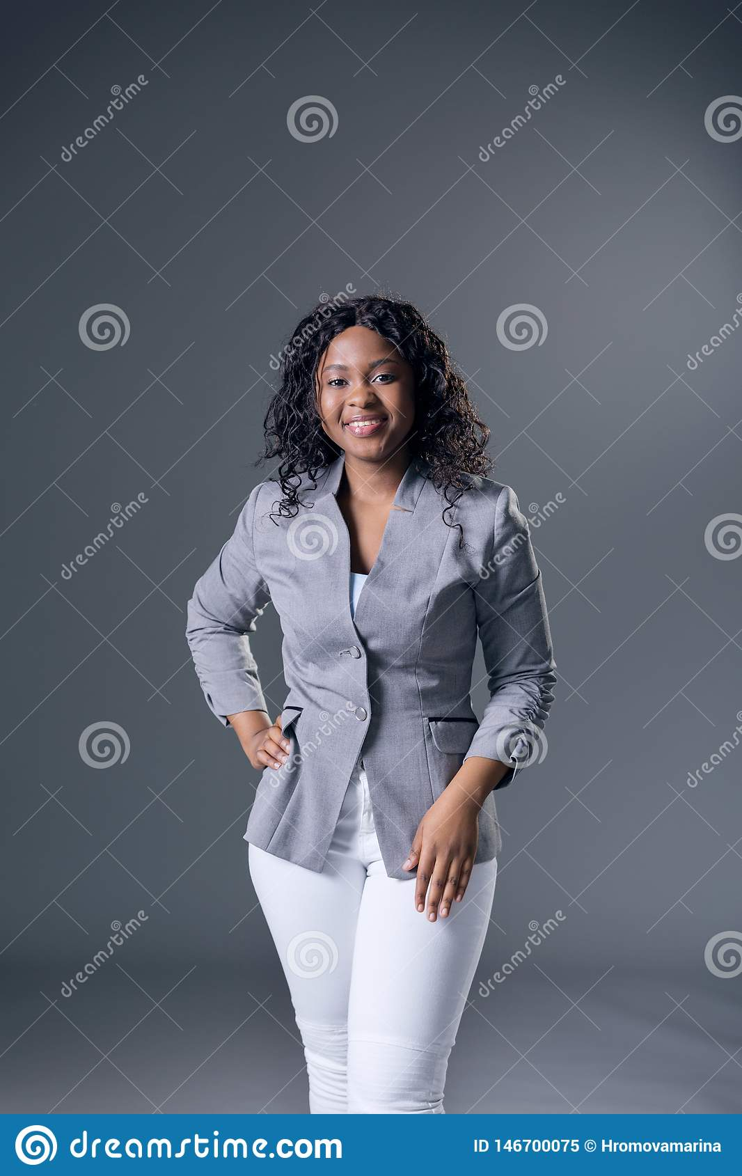 Dark-skinned beautiful woman a gray jacket with dark curly hair posing on a gray background.