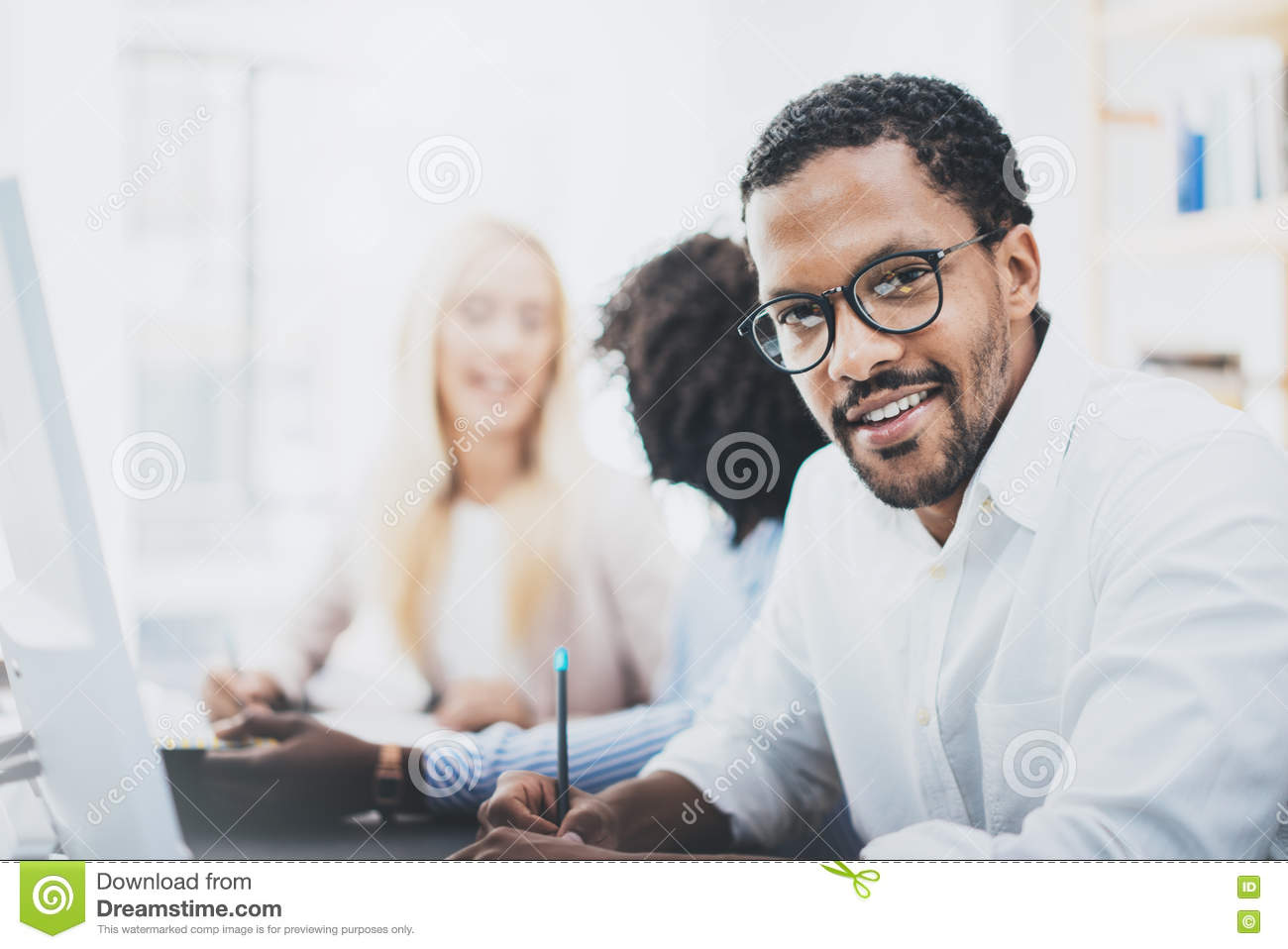 Dark skinned entrepreneur wearing glasses, working in modern office.African american man in white shirt looking and smiling at the