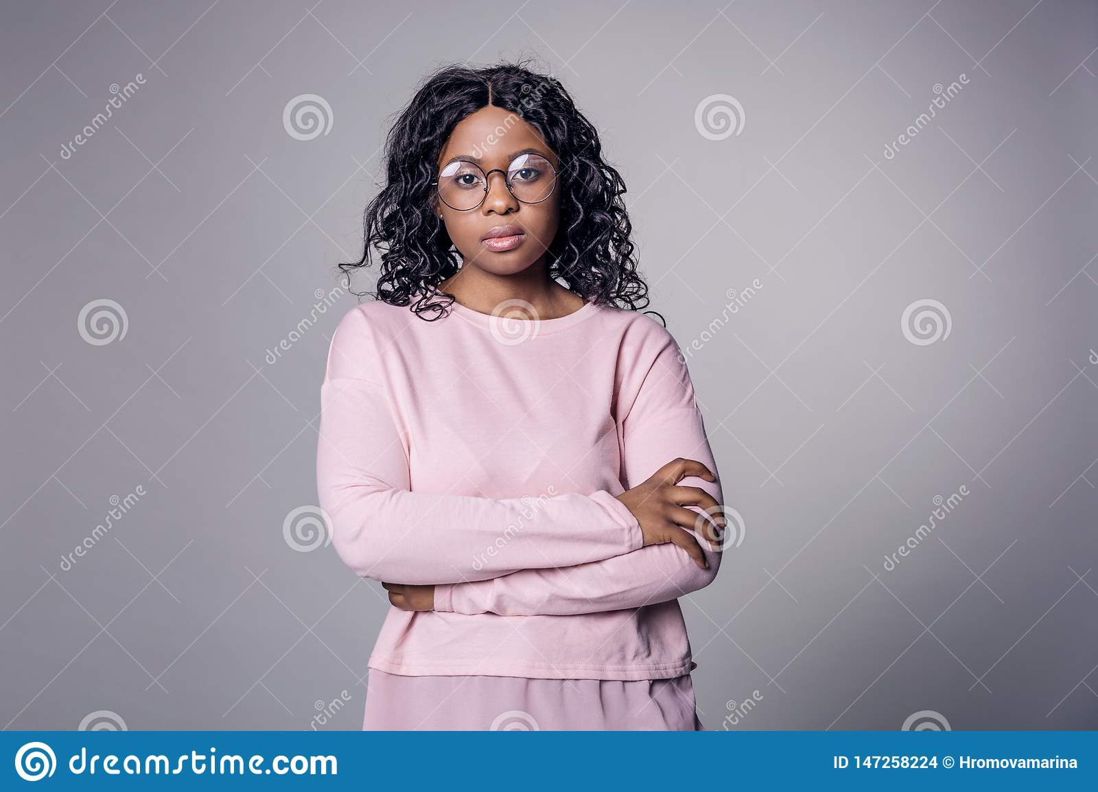 A dark-skinned girl in a pink jacket round glasses looks at the camera all the same located on a gray background.