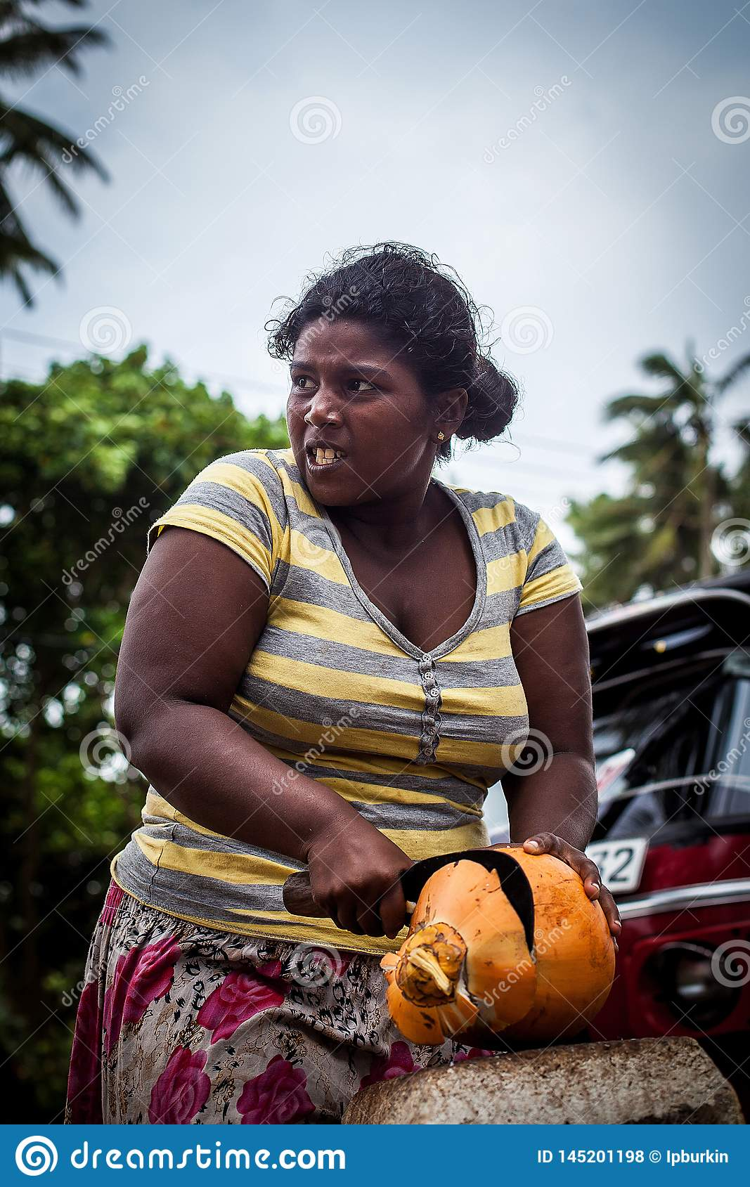 A dark-skinned woman cuts an orange coconut with a big knife. Working hard women. Strong and worthy woman doing hard job
