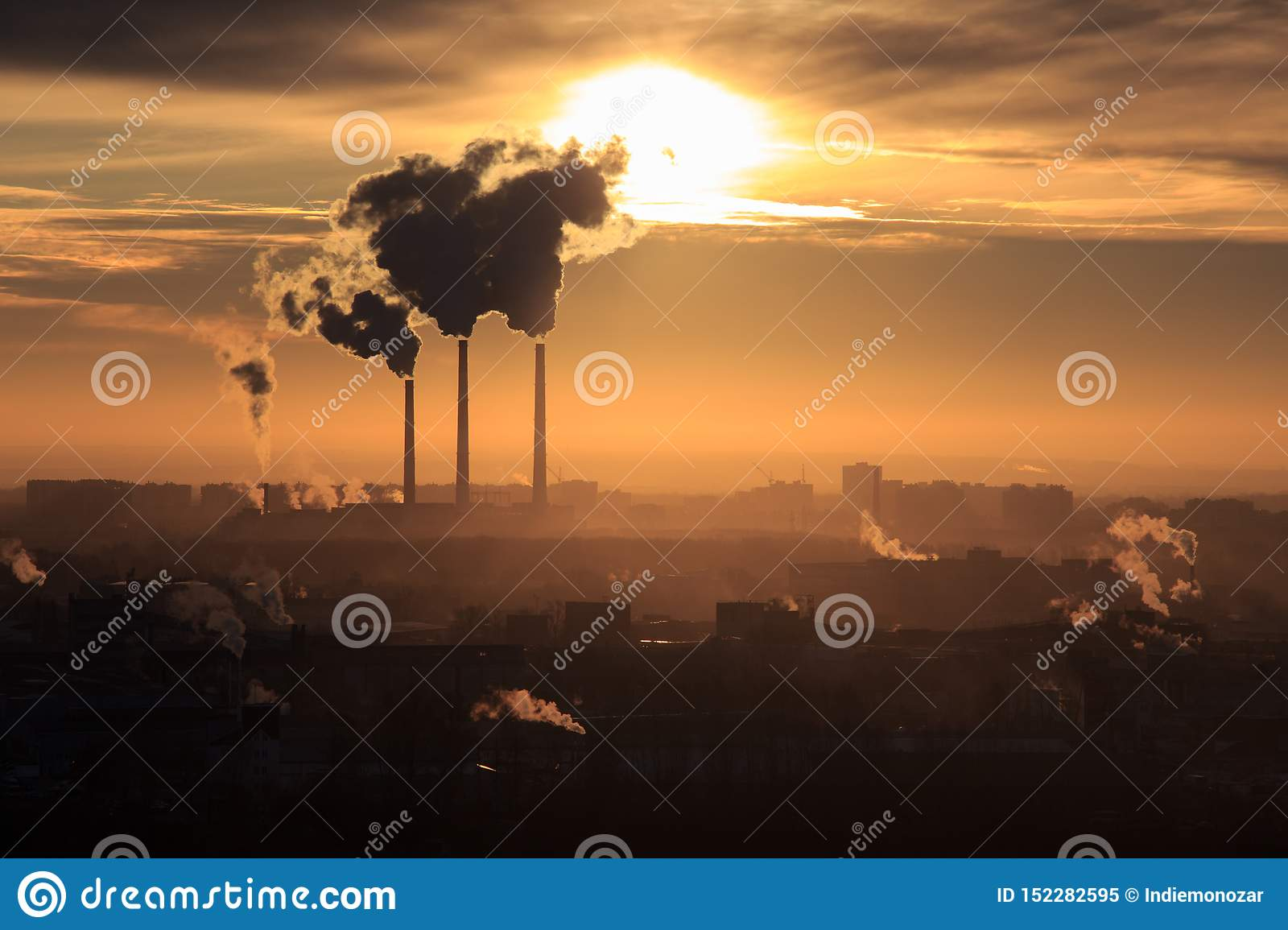 Dark smoke coming from the thermal power plant pipe. Factory smoke, polluting the atmosphere. Industrial zone in the city