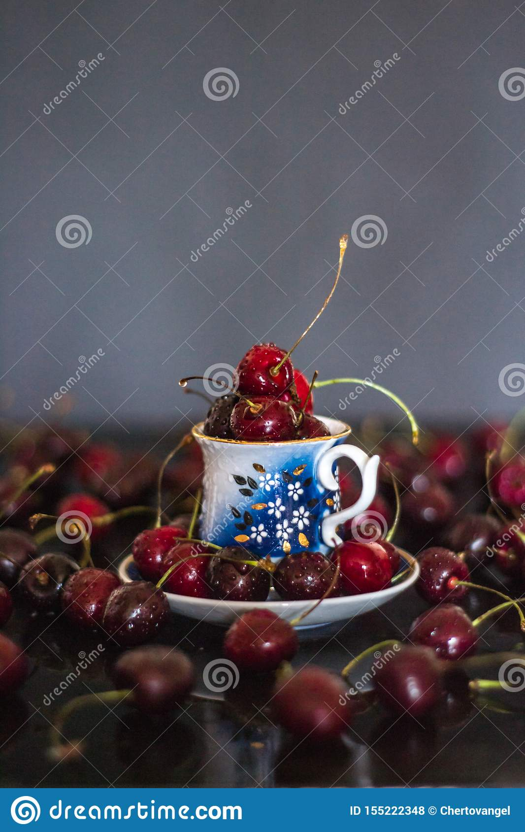 Dark stillife with porcelain cup of fresh cherries