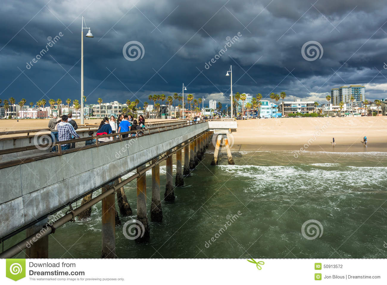 Dark storm clouds over the fishing pier and beach in for Fishing in los angeles