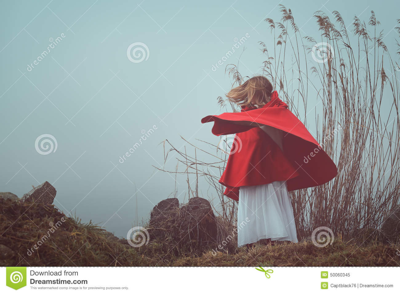 Dark and surreal portrait of a red hooded woman