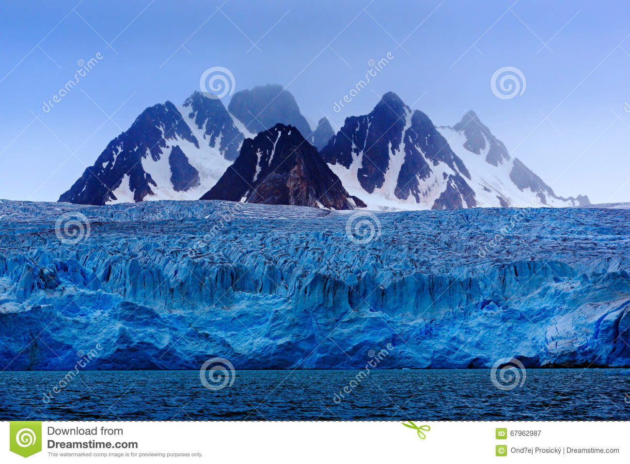 Dark winter mountain with snow, blue glacier ice with sea in the foreground, Svalbard, Norway, Europe