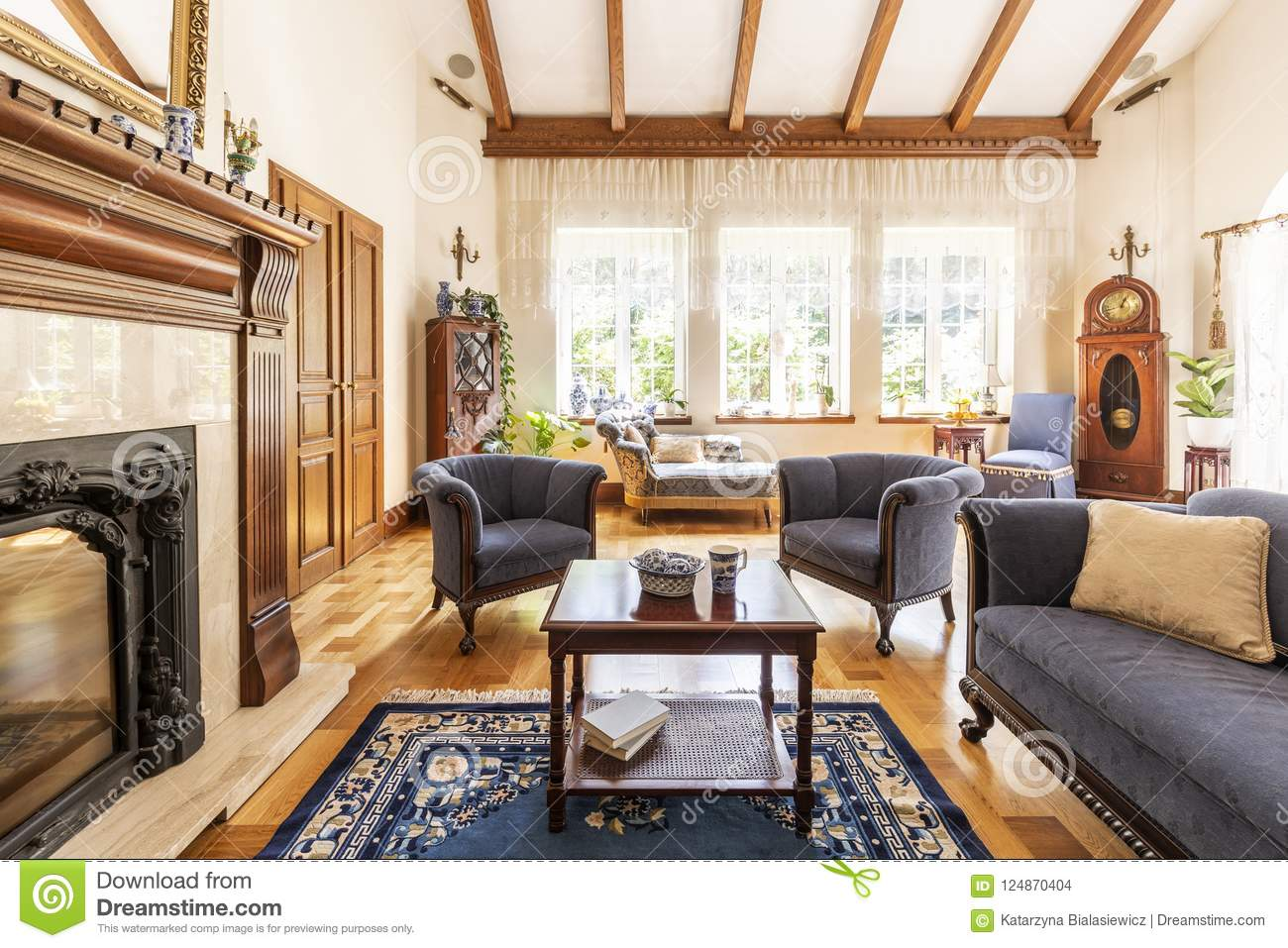 Dark wooden table on carpet between blue armchairs and sofa in luxury interior with fireplace. Real photo