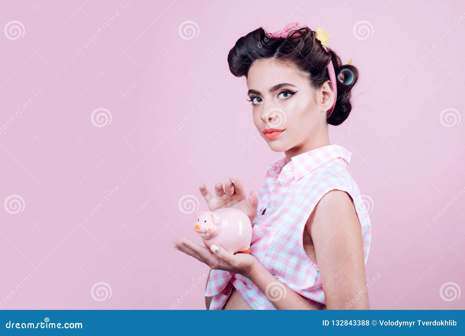 Darlehen Geld hausfrau Stift herauf Frau mit modischem Make-up Hübsches Mädchen in der Weinleseart Retro- Frau mit moneybox pinup
