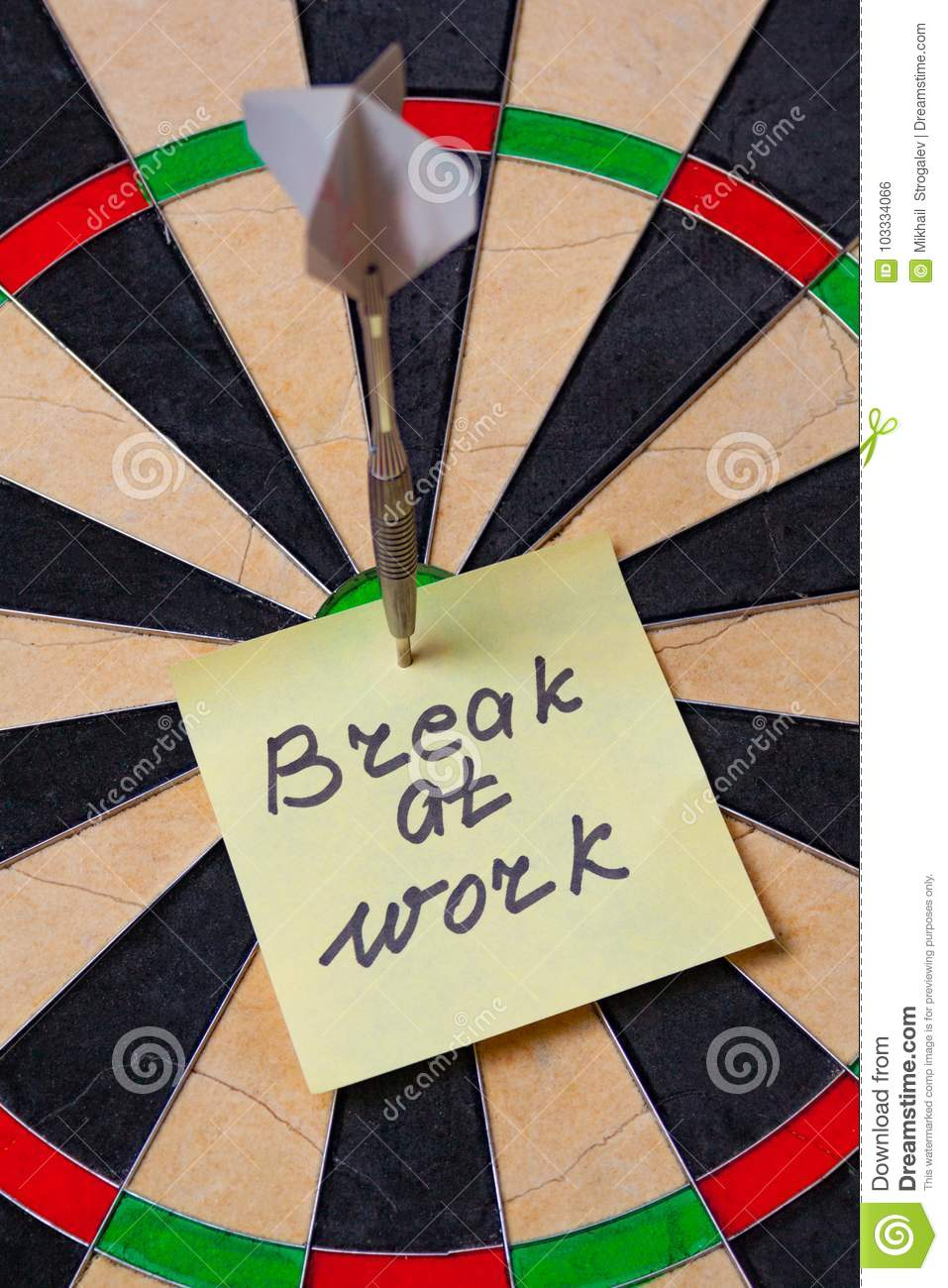 Dart hit the centre of target and attaches sticker with inscriptions  break at work  (concept of office work)