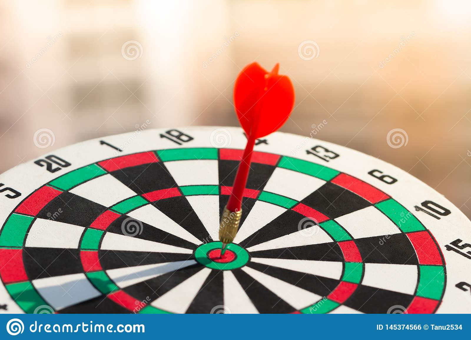 Darts arrow hitting in the target center of dartboard. concept business goal to marketing success.