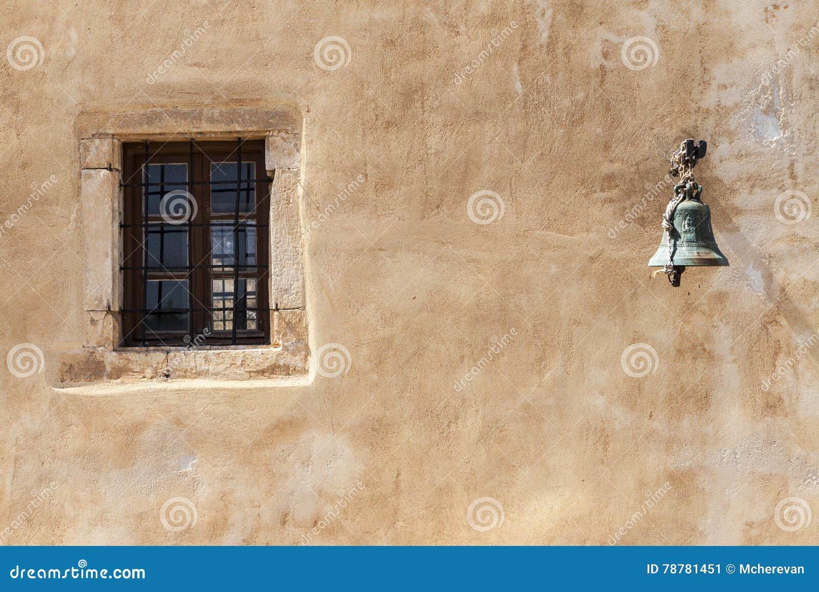 Das alte Gefängnismauerfenster mit Eisenstangen und Alarmglocke