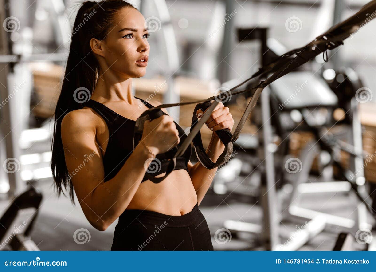 Das athletische dunkelhaarige M?dchen, das in der schwarzer Sportspitze und -kurzen Hosen gekleidet wird, arbeitet auf der Eignun