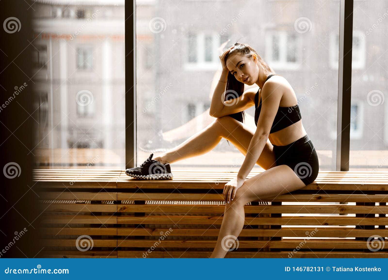 Das athletische dunkelhaarige M?dchen, das in der schwarzer Sportspitze und -kurzen Hosen gekleidet wird, sitzt auf einem h?lzern