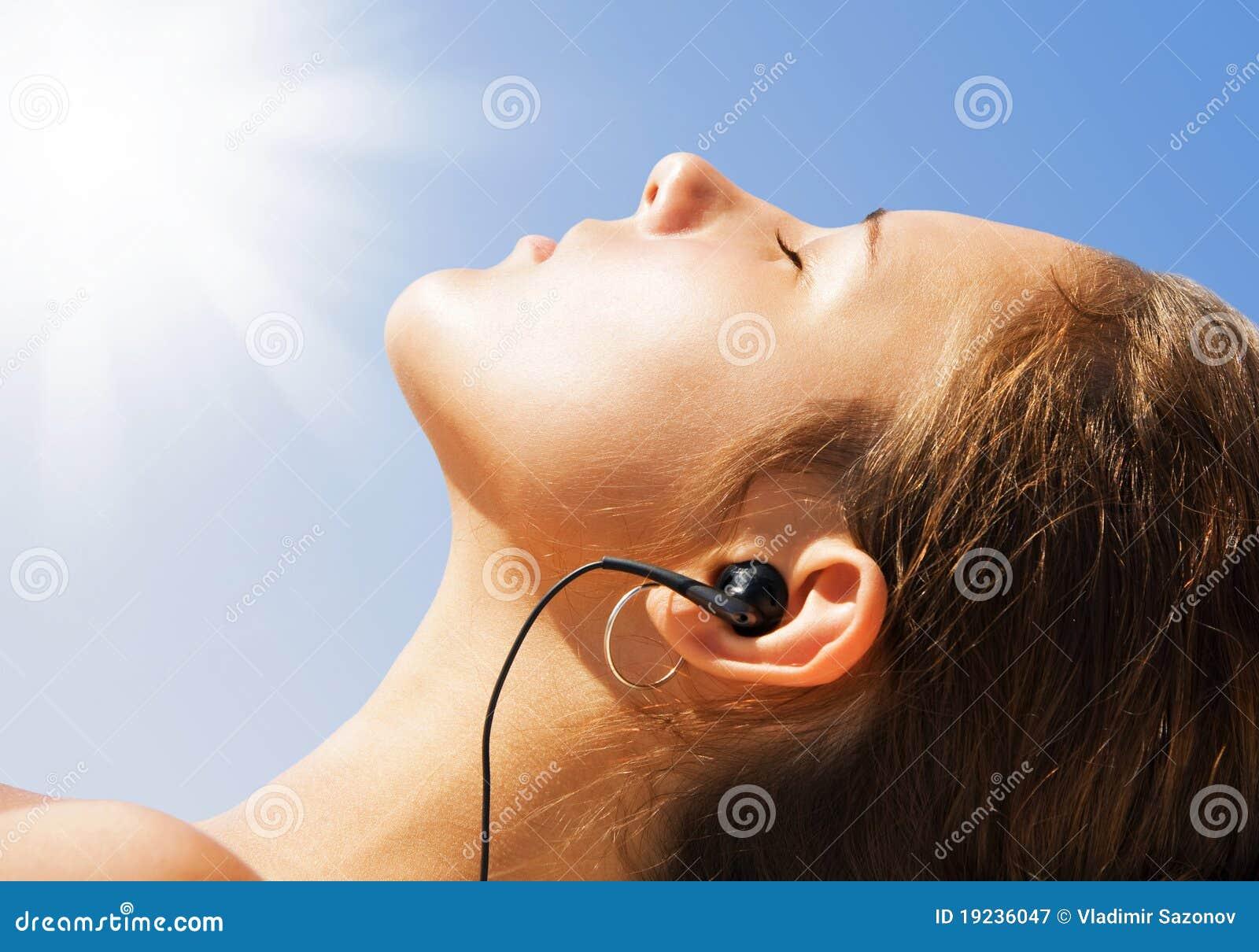Das attraktive entspannende Mädchen und nehmen auf Strand ein Sonnenbad.