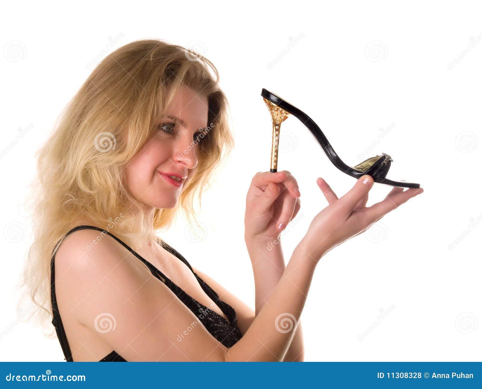 Das attraktive Mädchen mit Schuh in der Hand