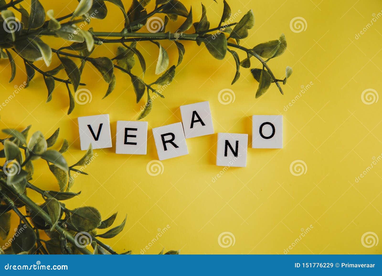 Das Aufschrift verano auf spanisch auf den Buchstaben der Tastatur auf einem gelben Hintergrund mit Niederlassungen von Blumen