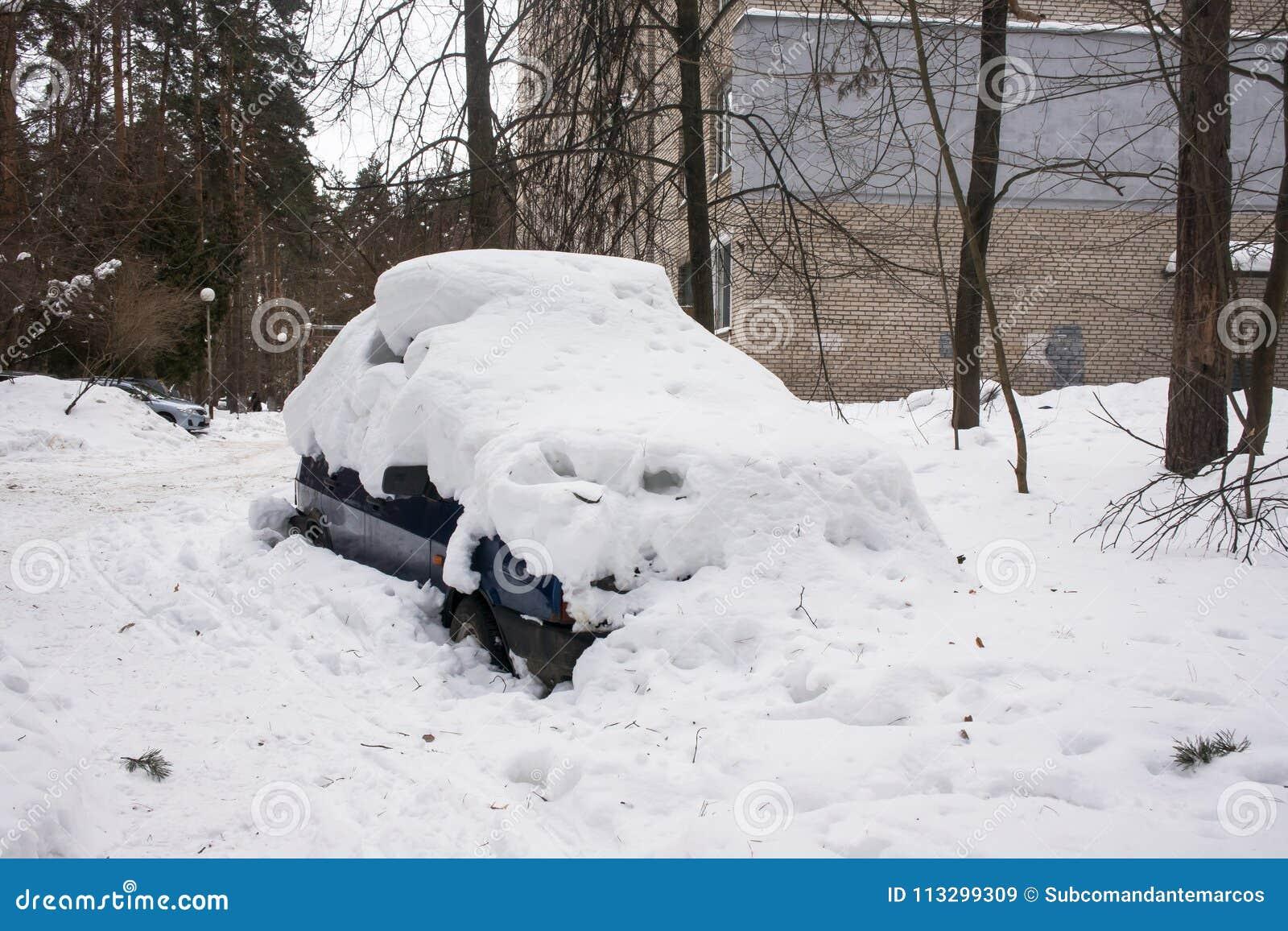 Das Auto, bedeckt mit starker Schneeschicht, im Yard des Wohnhauses in der provilcial Stadt