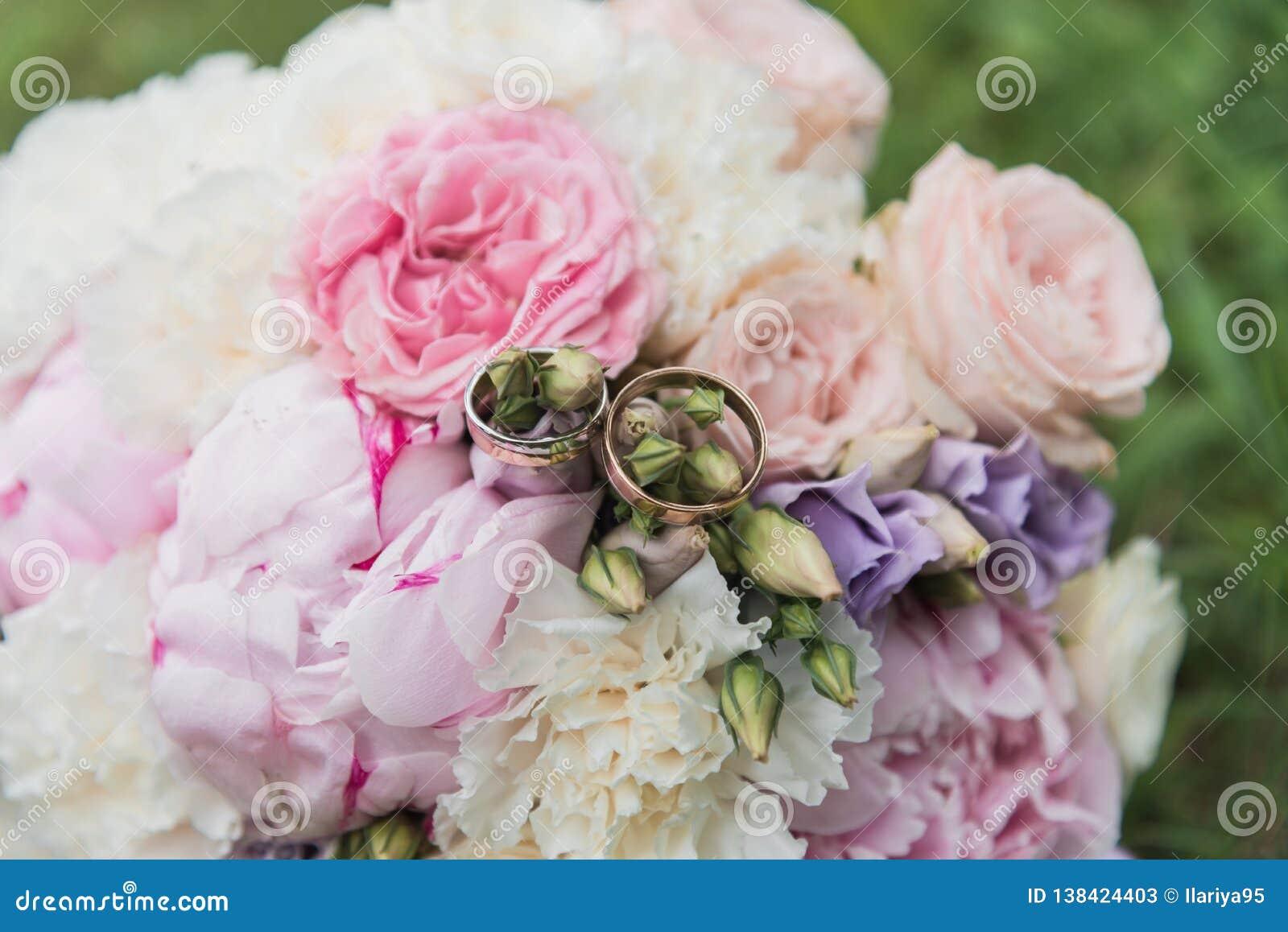 Das bride& x27; s-Blumenstrauß Schellt Jungvermählten Ein Blumenstrauß von Blumen mit Ringen