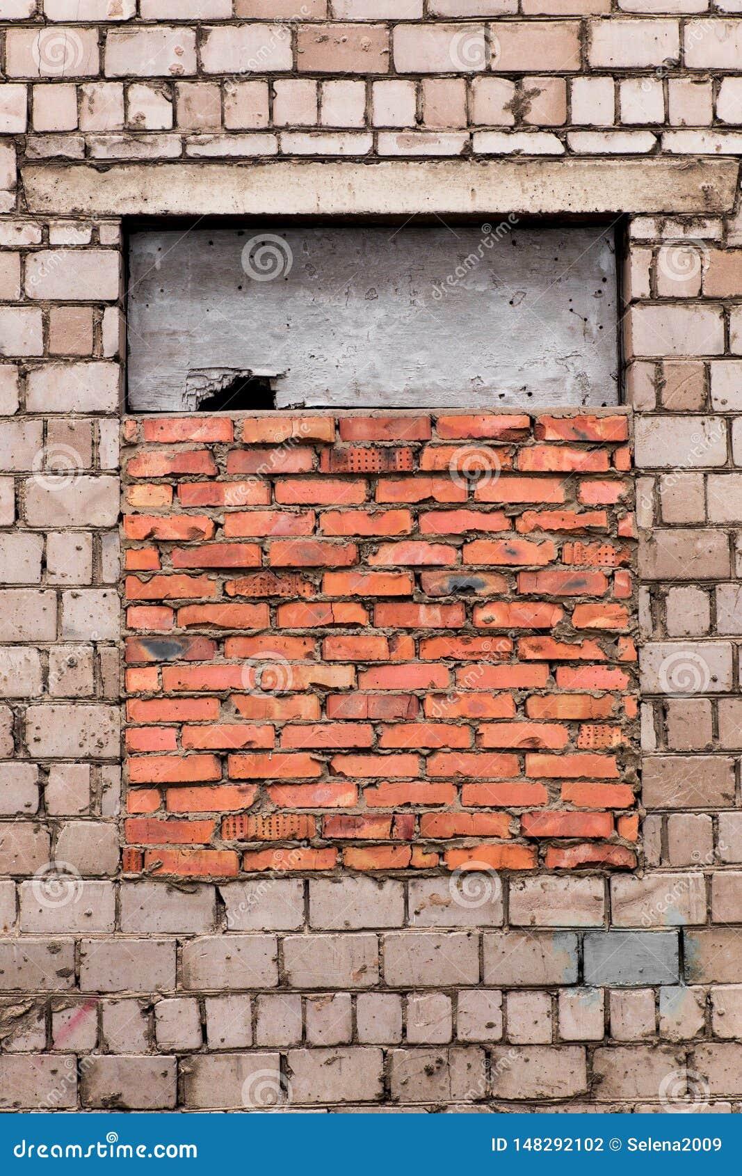 Das Fenster bricked oben Fenster ist gelegter Ziegelstein Graue Backsteinmauer mit einem Fenster gelegt mit rotem Backstein Das F