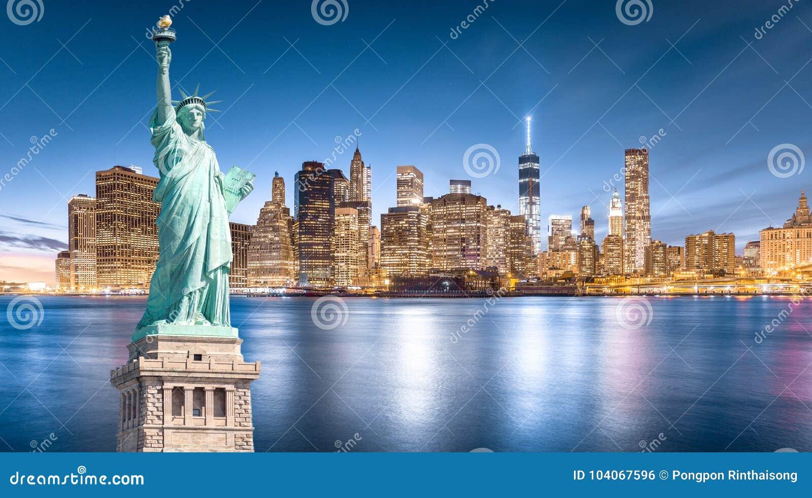 Das Freiheitsstatue mit Lower Manhattan-Hintergrund am Abend, Marksteine von New York City