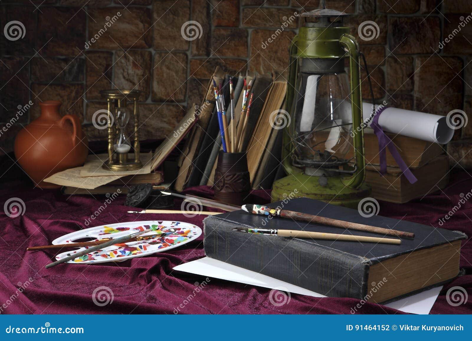 Das Gestell mit Bürsten liegt auf dem Tisch nahe der alten Öllampe Stilisiert als Retro- Stillleben Selektiver Fokus